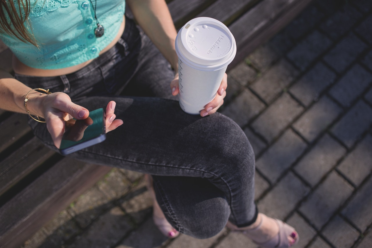 image of a woman with takeaway paper coffee cup